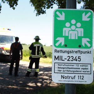 Hinter einem Schild für den Rettungspunkt stehen Rettungskräfte