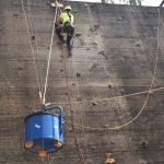 Ein Kletterer bewegt mit Seilen eine blaue Tonne