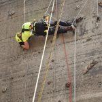Kletterer hängt quer an einer Betonwand