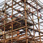 An einem alten Metallgerüst klettern viele Arbeiter