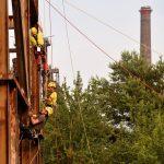 Drei Kletterer steigen an einem Eisengerüst auf