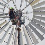 Industriekletterer vor einem amerikanischen Windrad