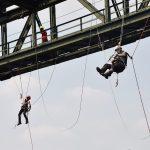 Zwei Personen gesichert an seinem unter einem Eisenträger