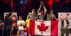 Three people with Canadian flags raise a trophy.