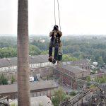 Ein Kletterer steigt in einem Industriegebiet nach oben