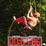 Hinter einer großen Digital Uhr, klettert eine Baumpfleger ein Seil nach oben