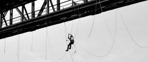 Kletterer hängt an einem Seil unter einem Gerüst