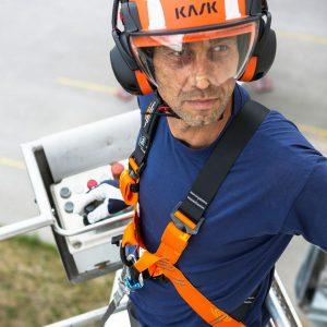 Arbeiter mit Helm und Fanggurt in einer Hubarbeitsbühne