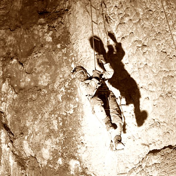 Old picture of a cave climber with old technique